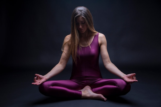 Young woman practicing yoga position in lotus flower, isolated on a dark background