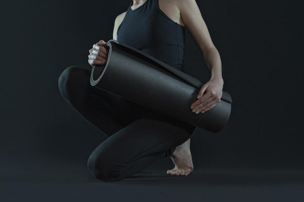 ヨガマットのヨガの位置を練習する若い女性