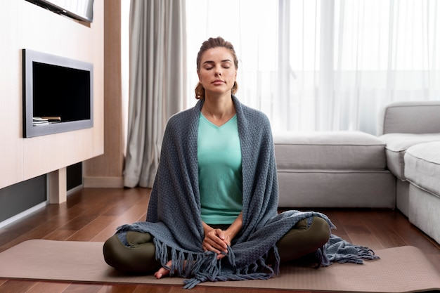 Young woman practicing yoga to relax