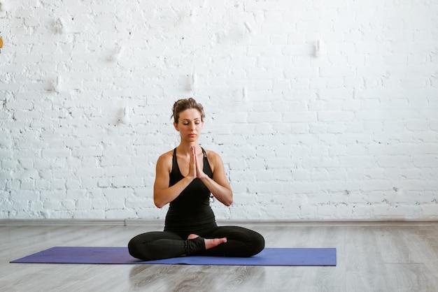 スポーツウェア屋内コーカサス州のトレーニングマットに座ってエクササイズに座ってヨガを練習している若い女性...
