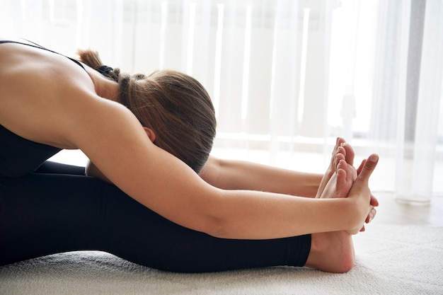 Young woman practicing yoga sitting in seated forward bend exercise paschimottanasana pose working