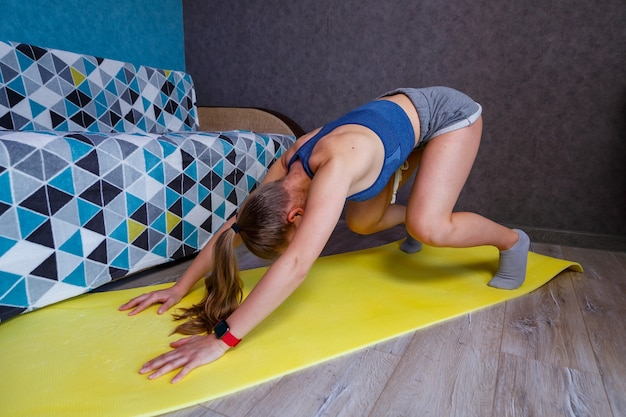 Young woman practicing yoga, standing in dog pose face down, exercises adho mukha svanasana, girl in gray sportswear, shorts and a bra, exercising at home or in a yoga studio, body stretching