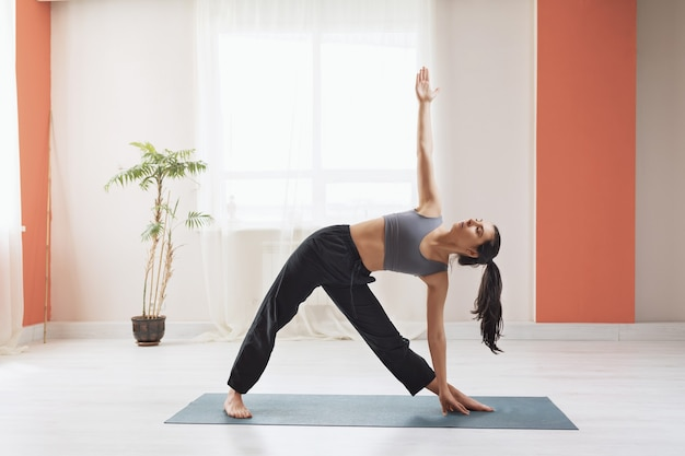 Young woman practicing yoga standing on the mat performs the exercise utthita trikonasana triangle pose