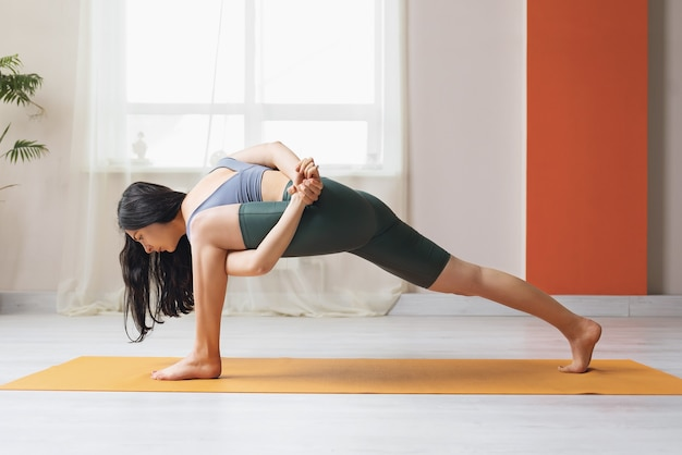 A young woman practicing yoga standing on a mat performs in the studio the exercise utthita parshvakonasana with a grip an extended lateral angle pose