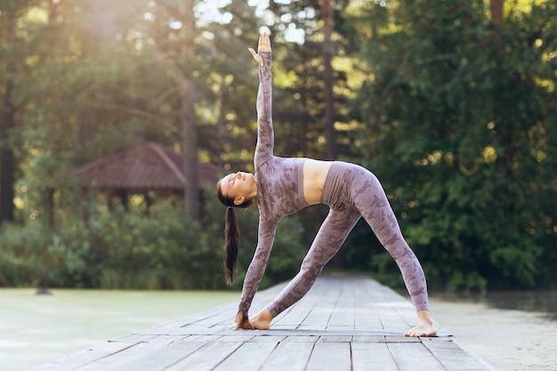 Young woman practicing yoga on a sunny morning doing the exercise uthita trikonasana triangle pose