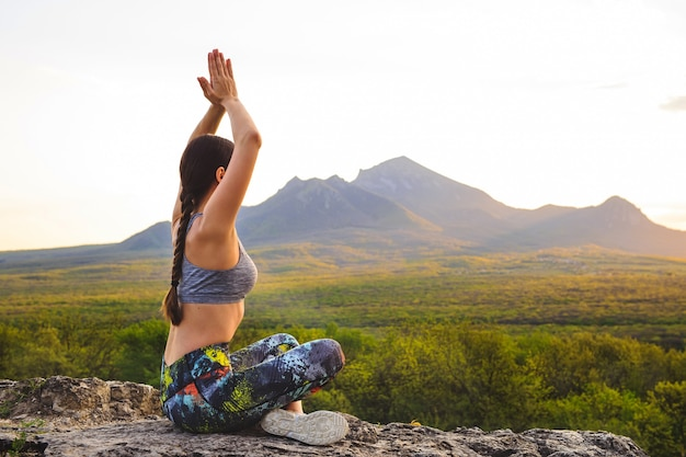 Young woman practicing yoga at sunset in beautiful mountain location.