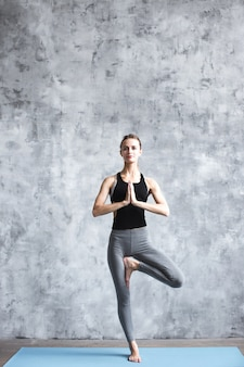 Young woman practicing yoga vrikshasana in gym