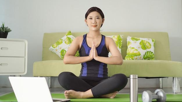 Молодая женщина упражнениями йоги с акцентом дома