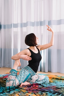 Young woman practicing yoga with mudra gesture