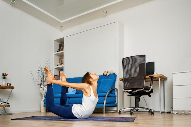Молодая женщина, практикующая йога дома, делает позу с луком на коврике
