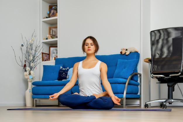 Молодая женщина практикует йога дома, сидя в легкой позе на коврике