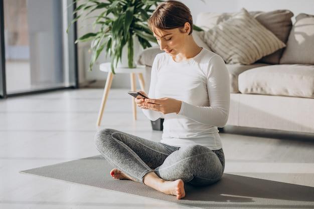 マットの上で自宅でヨガを練習する若い女性