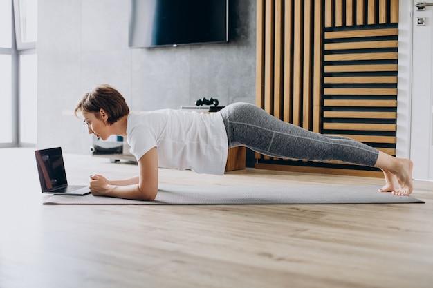 マットの上で自宅でヨガを練習している若い女性