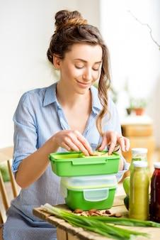 Молодая женщина готовит еду в зеленых ланч-боксах, сидя на столе в помещении