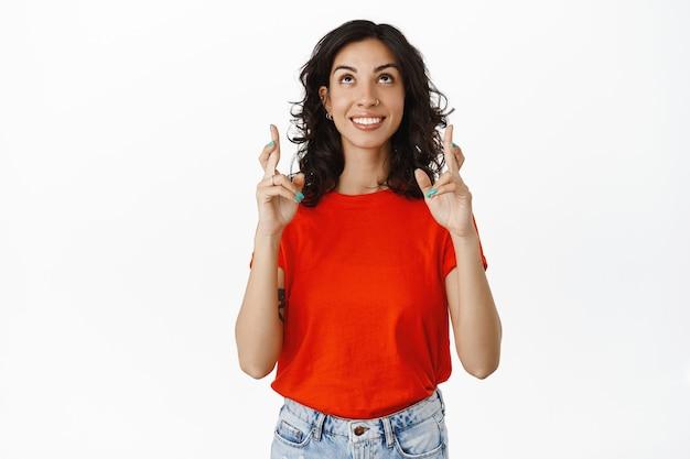 Giovane donna che prega, alzando lo sguardo con le dita incrociate, esprimendo desiderio, sperando in buona fortuna, in piedi in maglietta rossa su bianco