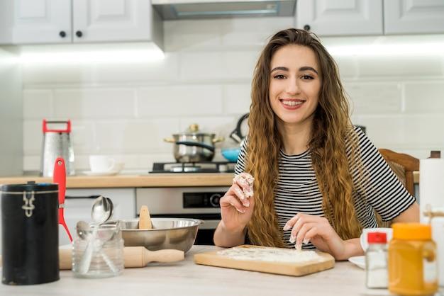 若い女性は台所のテーブルでおいしい食品練り粉を準備します。異なる材料で料理をする