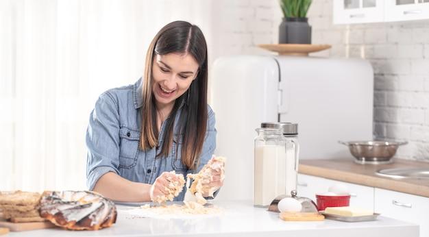 Молодая женщина готовит тесто для домашней выпечки на просторной светлой кухне.