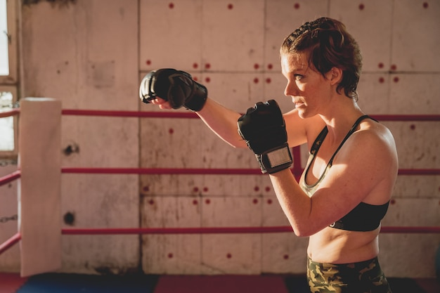 Young woman prepares for matches mma in the cage. training in a sport hall