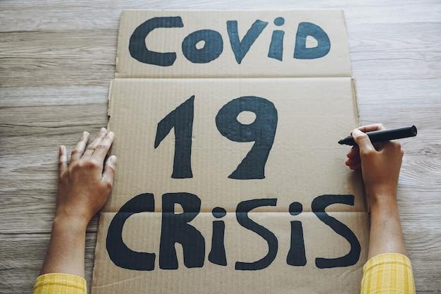 Молодая женщина готовит баннер для протеста covid 19 экономического кризиса