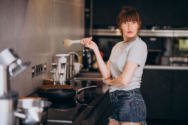 Young woman preparing breakfast in kitchen in the morning