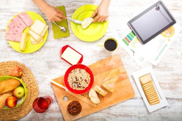 栄養に関するオンライン情報を取得しながら朝食を準備している若い女性。