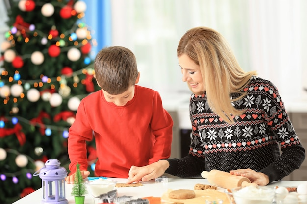 Young woman preparing christmas cookies with little son in kitchen