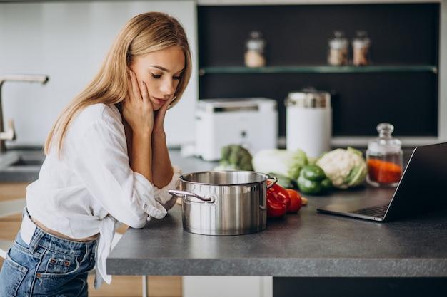 台所で食事を準備する若い女性