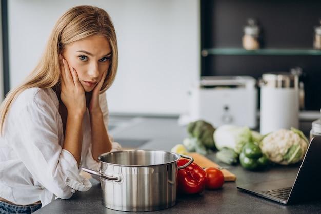 Giovane donna che prepara il cibo in cucina