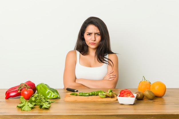 Young woman preparing a healthy meal frowning face in displeasure, keeps arms folded.