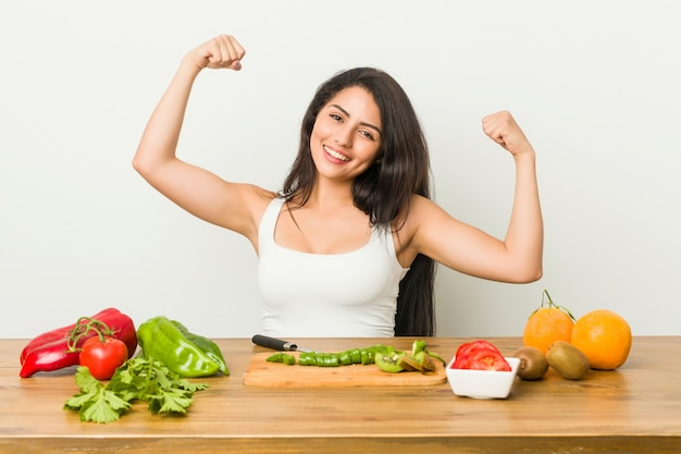 Young woman preparing a healthy meal showing strength gesture with arms, symbol of feminine power
