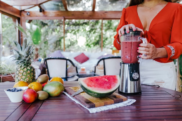 Young woman preparing a healthy recipe of diverse fruits, watermelon, orange and blackberries. using a mixer. homemade, indoors, healthy lifestyle