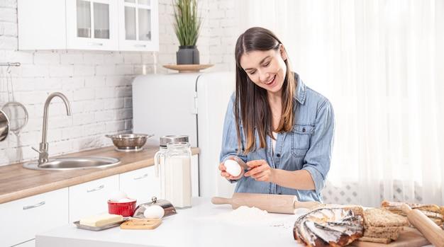 Молодая женщина готовит домашнюю выпечку на просторной светлой кухне