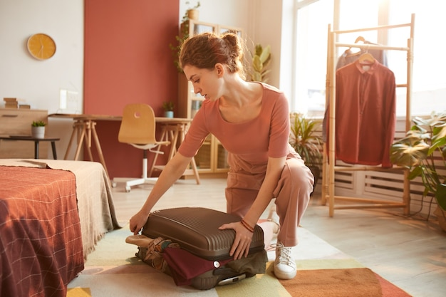 Young woman preparing for journey in the room packing her suitcase with clothes