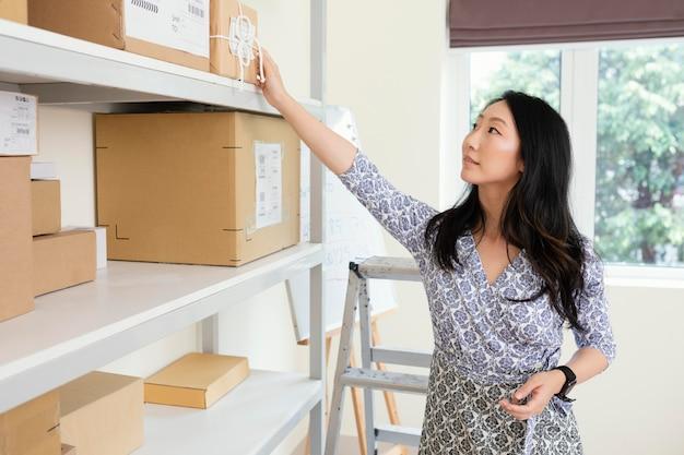 Giovane donna che prepara i pacchi per la consegna