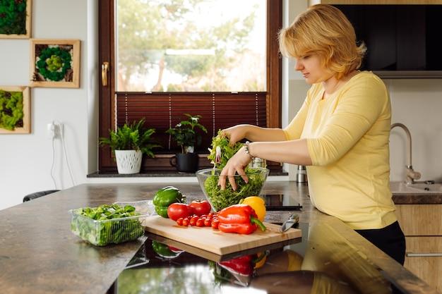 Молодая женщина готовит салат из свежих листьев рукколы и овощей для своей семьи на кухне. ингредиенты перец, помидоры. концепция здорового и правильного питания. веганская еда