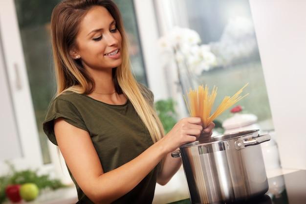 キッチンでスパゲッティを準備する若い女性
