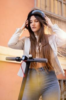 도시에서 전기 스쿠터를 타고 준비하는 젊은 여자