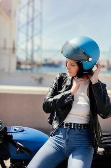 Молодая женщина готовится к поездке на мотоцикле в городе