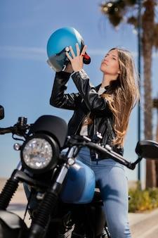 도시에서 오토바이 타고 준비하는 젊은 여자