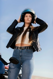 街でバイクに乗る準備をしている若い女性