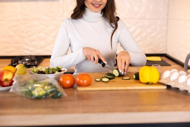 彼女の台所で野菜サラダを準備している若い女性。健康的なライフスタイルの概念混合野菜と美しい女性。