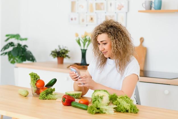 彼女の台所で野菜サラダを準備している若い女性。