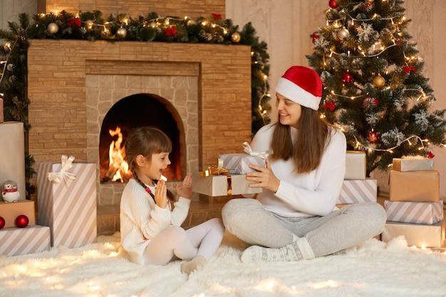 クリスマスの朝に彼女の小さな娘にクリスマスプレゼントを提示する若い女性