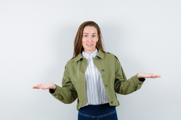Young woman presenting or comparing something in shirt, jacket and looking confident. front view.