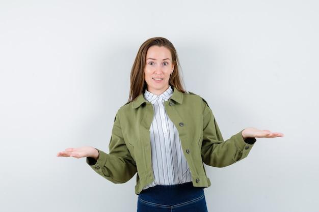 シャツ、ジャケットで何かを提示または比較し、自信を持って見える若い女性。正面図。 無料写真