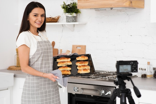 Young woman presenting pastries on camera