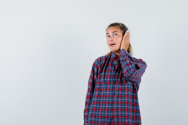 Young woman pressing hands on ear in checked shirt and looking pretty