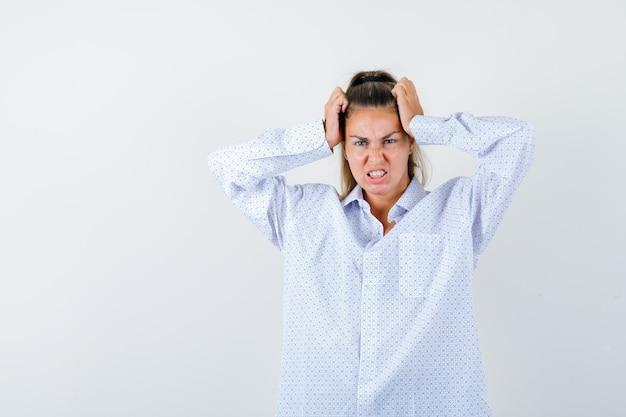 Молодая женщина зажимает уши руками, морщится в белой рубашке и выглядит сердитой