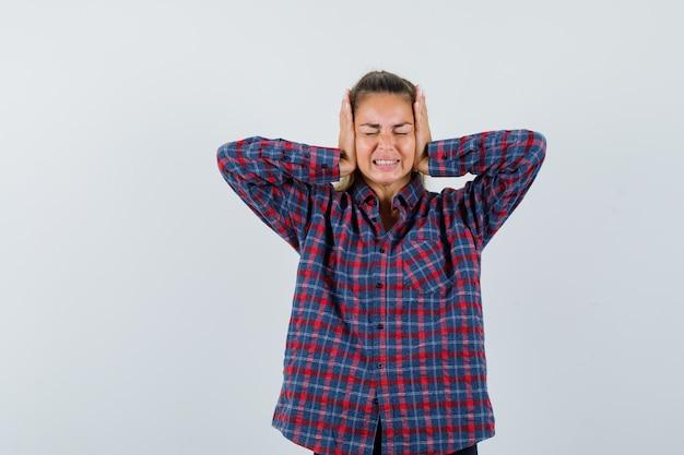 Молодая женщина в клетчатой рубашке сжимает руки уши и выглядит раздраженной