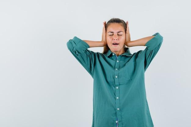 Молодая женщина в зеленой блузке сжимает руки уши и выглядит спокойной